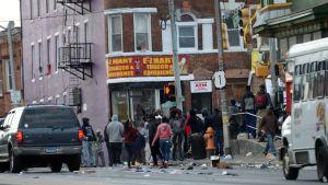 En grupp människor utanför en butik i Baltimore. Skräp ligger på gatan.