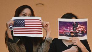 Två demonstranter håller upp bilder på USA:s flagga och president Donald Trump