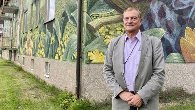 En äldre man står framför en muralmålning på en husvägg. Han ler och tittar in i kameran.