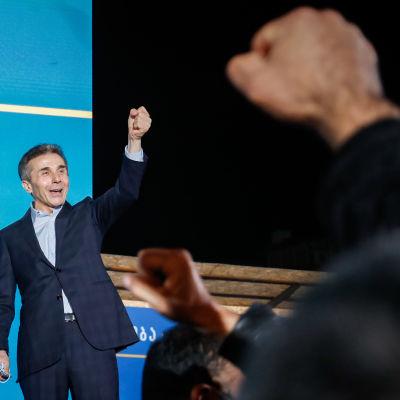 Bidzina Ivanishvili nostaa kätensä pystyyn yleisön edessä