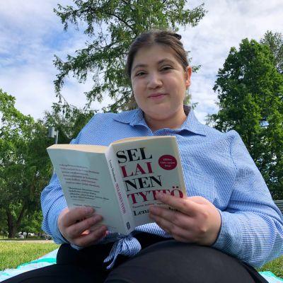 Tummahiuksinen nainen hymyilee kirjan takaa kuvaajalle.