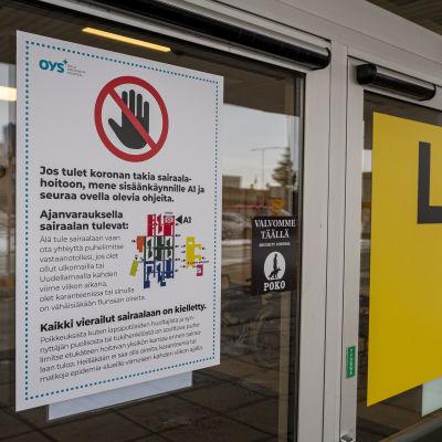 Oulun yliopistollisen sairaalan ovessa ohje