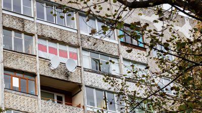 Den gamla belarusiska flaggan i vitt och rött hänger i ett fönster i ett höghus.