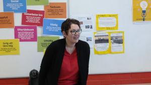 Studiehandledare Maarit Munkki står framför en anslagstavla i ett klassrum