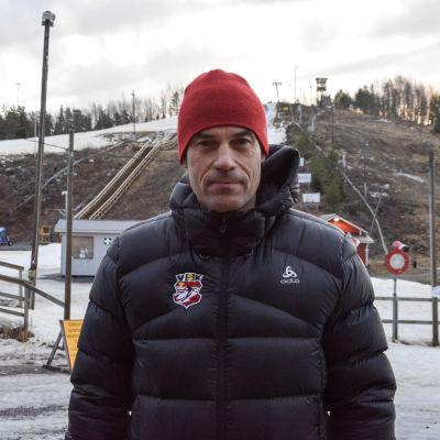Man i vinterjacka och röd mössa tittar in i kameran. I bakgrunden en snöfattig slalombacke.