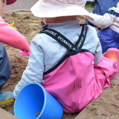 Några barn leker i en sandlåda.