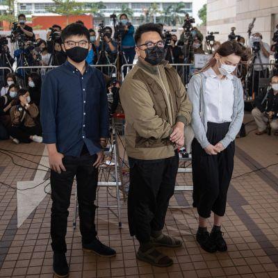 Kolme aktivistia kuvaajajoukon edessä.