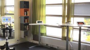 rum med stora fönster och bord med pekplattor, en bokhylla och en motionscykel med pekskärm