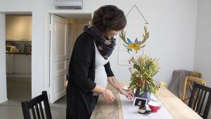 Emilia Jansson som står vid ett bord, och håller i ultraljudsbilder som föreställer hennes barn.