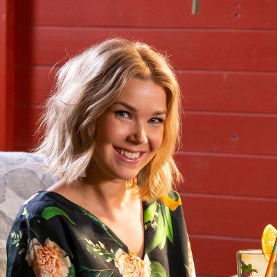 Juontaja-toimittaja Tuija Pehkonen istuu saunan edustalla, katsoo kameraan ja hymyilee.