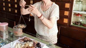 En kvinna lägger något torrt material i en liten vågskål och i andra handen håller hon en liten tyngd. På bordet finns olika sorter av torkat material och bakom henne finns en hylla med många små lådor och en del glasburkar.