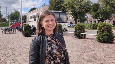 En kvinna står på Lovisa torg, ler och tittar in i kameran.