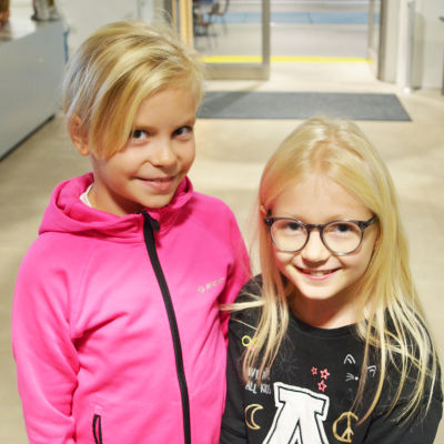 Två unga flickor tittar in i kameran och ler.