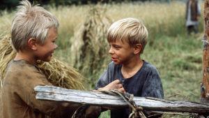 Pikkupojat juttelemassa, taustalla viljapeltoa ja heinäsuovia