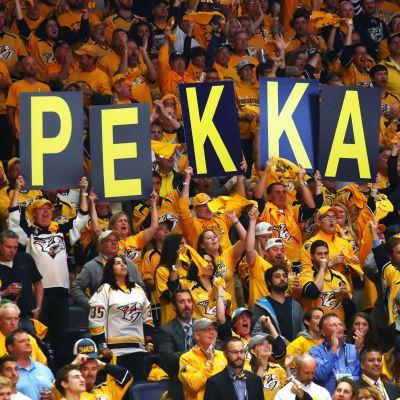 Supportrar håller upp skyltar med P-E-K-K-A.