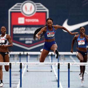 Dalilah Muhammad hoppar över en häck med två löpare snett bakom sig.