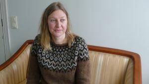 Bildkonstnär Heidi Lampenius sitter i en gammal soffa inne i Villa Snäcksund.