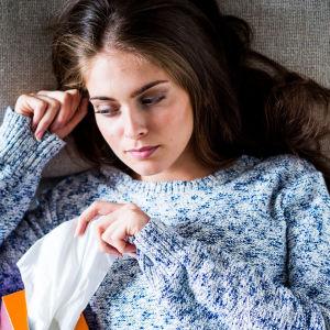 En kvinna ligger i sängen och gråter