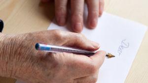 Gammal person skriver.