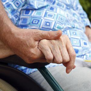 En äldre person i rullstol håller en vårdare i handen.