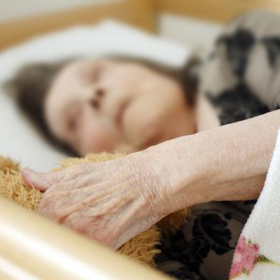 En äldre kvinna ligger i en sjukhussäng.