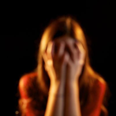 En kvinna håller händerna för ögonen.