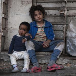 Två små barn sittande bland skräpet på en gata.