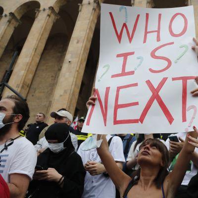 """""""Kuka on seuraava"""" kysytään mielenosoittajan kyltissä Georgian pääkaupungissa Tbilisissä."""