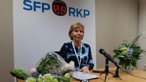 En leende Anna-Maja Henriksson med blombuketter på bordet och Sfp-plansch i bakgrunden.