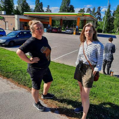 Två kvinnor står en solig sommardag framför en bensinstation.