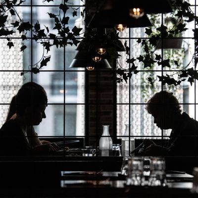 Ihmisiä syömäss ravintolassa.