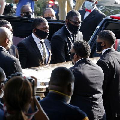 Flera män i kostym står runt en kista.