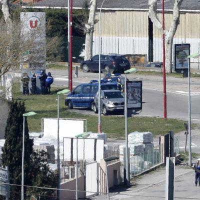 Bild av gatan vid köpcentret i Trèbes där gisslandrama pågår. Flera poliser står stationerade på gatan.