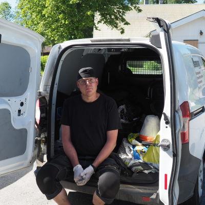 Esa Päiväkumpu istuu pakettiauton takapuskurilla.