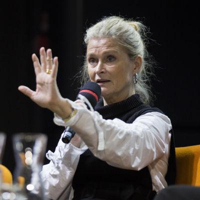 Närbild på Lena Endre som håller upp ena handen och pratar i mikrofon.
