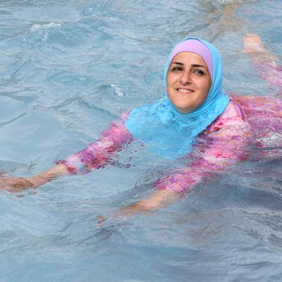 En turkisk ung kvinna simmar iklädd täckande burkini.