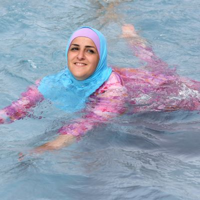 En ung kvinna simmar i burkini i en simbassäng i Berlin år 2012.