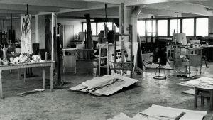 Suuri piirustusluokka, jossa papereita lattialla ja maalaustelineet odottavat kankaita, oppilaita ei näy missään.