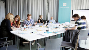 Ihmisiä ryhmätöissä pöydän ääressä neuvotteluhuoneessa