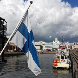 Södra hamnen i Helsingfors år 2015. Finlands flagga i förgrunden och bland annat Helsingfors domkyrka i bakgrunden.