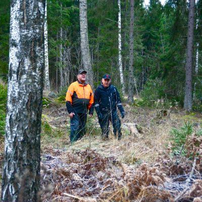 Två män i arbetskläder står i en skog.
