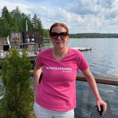 Nainen seisoo terassilla veden äärellä.