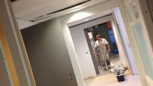 Målare i vit overall står i korridor i kontorslokal som renoveras, målarhink och -rulle på golvet.
