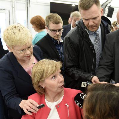 Anna-Maja Henriksson sitter vid ett bord i röd dräkt omgiven av journalister som sticker fram mikrofoner.