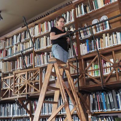 Nainen seisoo kirjaston ylätasanteella, edessä tikkaat
