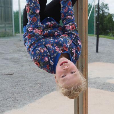 Neljäsluokkalainen Vilma Tiilikainen roikkuu pää alaspäin kiipeilytelineessä Kummun koulun pihamalla.
