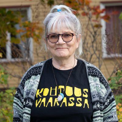 Kirjailija Ulla Vaarnamo hymyilee puun alla.