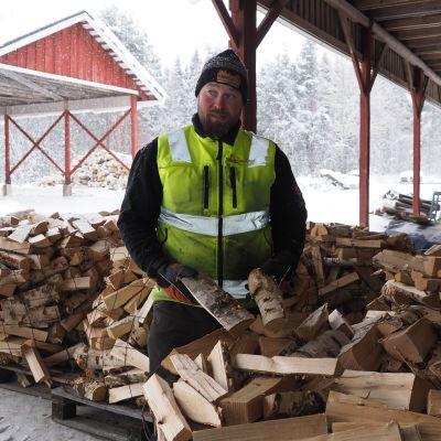 Halkokauppias Kalle Nisonen seisoo halkolavojen vieressä.