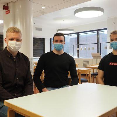 Kolme opiskelijaa istuskelee yliopiston aulassa.