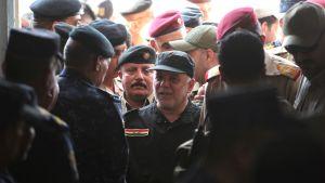 Iraks premiärminister omringad av säkerhetspersonal i Mosul.